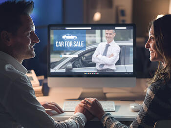 middle-aged couple looking online for a car